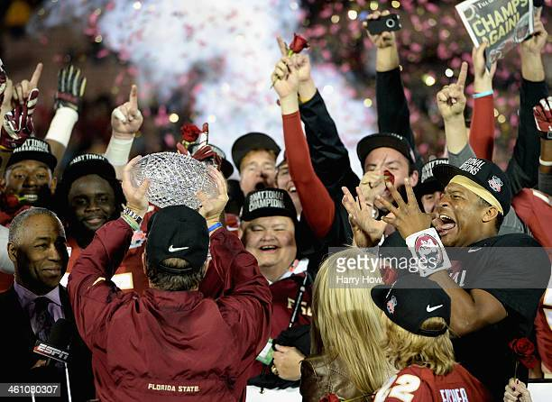 Florida State Seminoles head coach Jimbo Fisher holds the Coaches' Trophy as quarterback Jameis Winston looks on after defeating the Auburn Tigers...