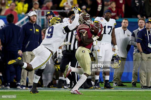 Florida State Seminoles running back Dalvin Cook makes a reception as Michigan Wolverines linebacker Mike McCray defends during the first quarter of...
