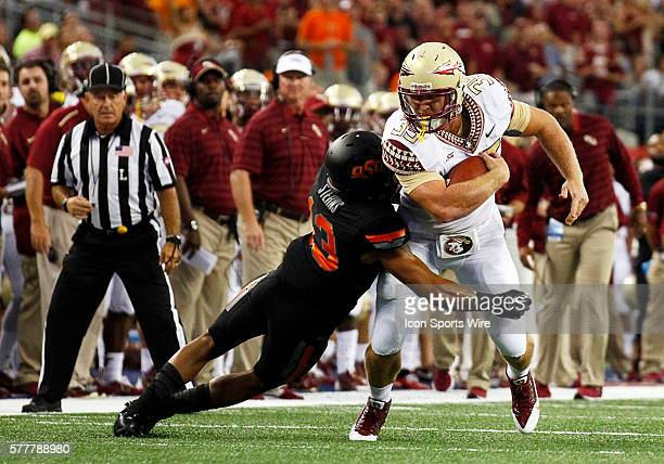 Florida State Seminoles tight end Nick O'Leary is tackled by Oklahoma State Cowboys safety Jordan Sterns during a NCAA football game between the...