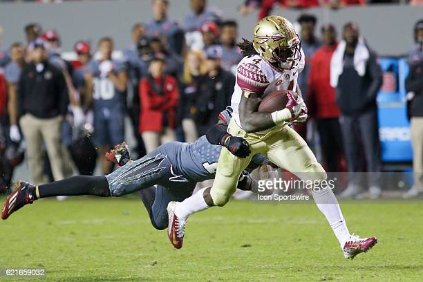 Florida State tailback Dalvin Cook runs the ball and is tackled by NC State safety Josh Jones during the second half between the Florida State...