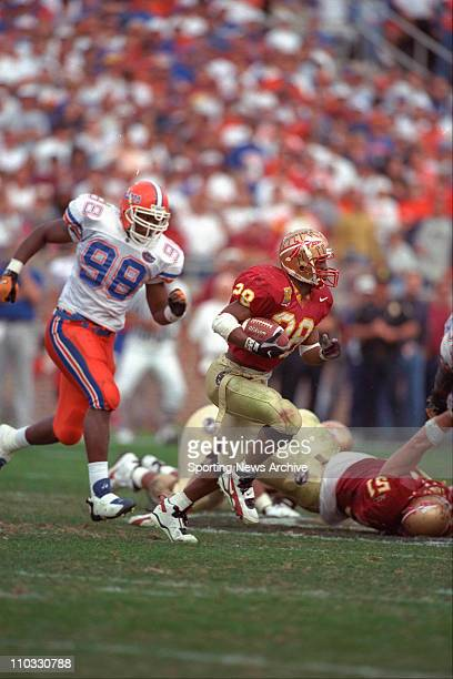 Florida State tailback Warrick Dunn carrying the ball while Florida defensive end Anthony Mitchell pursues him during a game on November 30 1996 in...