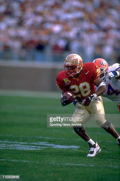 Florida State tailback Warrick Dunn fights forward for yardage as Florida safety Lawrence Wright is tackling him during a game on November 30 1996 in...