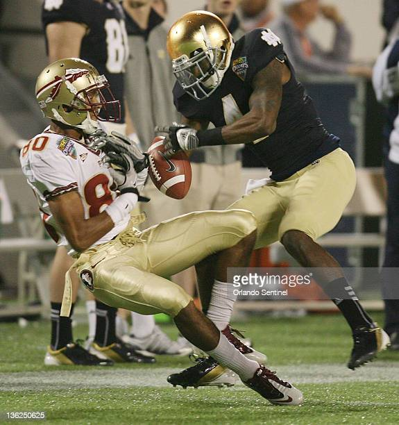 Florida State wide receiver Rashad Greene has the ball knocked out of his hands by Notre Dame cornerback Gary Gray during the Champs Sports Bowl at...