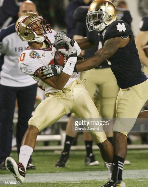 Florida State wide receiver Rashad Greene pulls in a key pass against Notre Dame cornerback Gary Gray during the Champs Sports Bowl at the Florida...