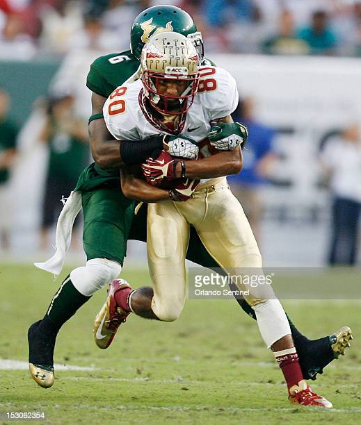 Florida State wide receiver Rashad Greene runs with a pass as he's tackled by South Florida defensive back Kayvon Webster at Raymond James Stadium in...