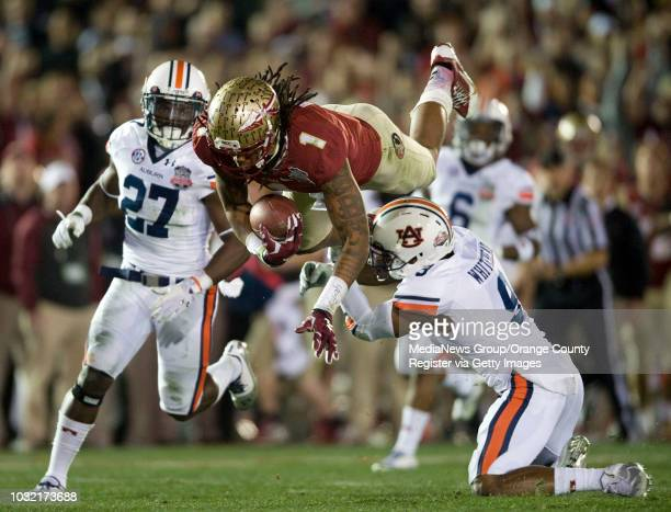 Florida State's Kelvin Benjamin gets some air as he makes a catch despite the effordts of Auburn's Jermaine Whitehead right and Robenson Therezie...