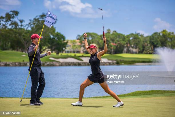 Florida Tech Women's Golf coaches Chris Saltmarsh and Sophomore Megan Dennis celebrate on the 18th hole after Dennis completes her final round....