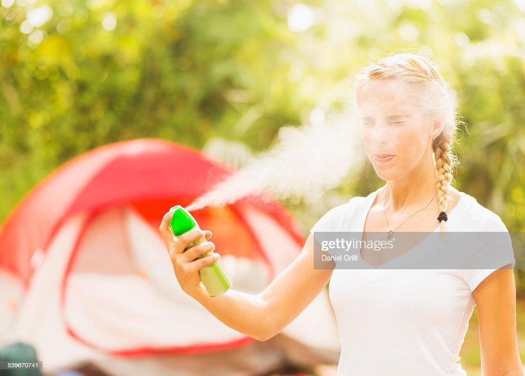 USA, Florida, Tequesta, Woman spraying head with bug spray : Stock Photo