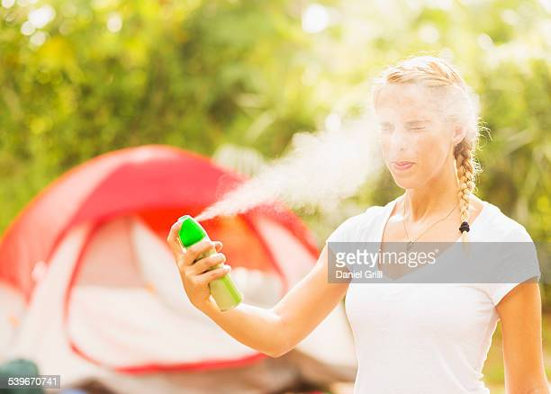 USA, Florida, Tequesta, Woman spraying head with bug spray