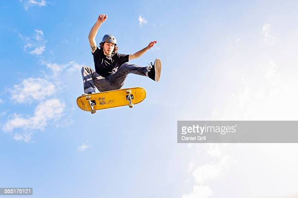usa, florida, west palm beach, man jumping on skateboard against sky and clouds - skateboard ストックフォトと画像