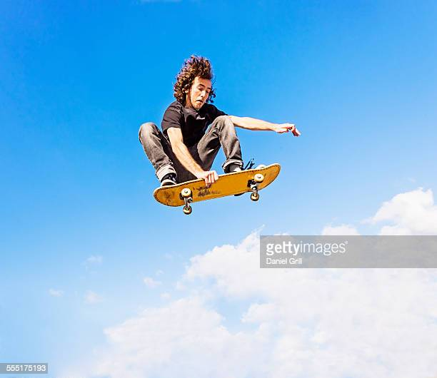 USA, Florida, West Palm Beach, Man jumping on skateboard against sky and clouds