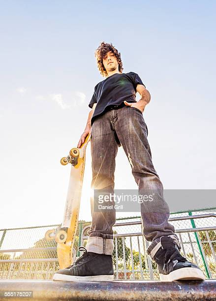 usa, florida, west palm beach, man leaning on skateboard in skatepark - vista de ángulo bajo fotografías e imágenes de stock