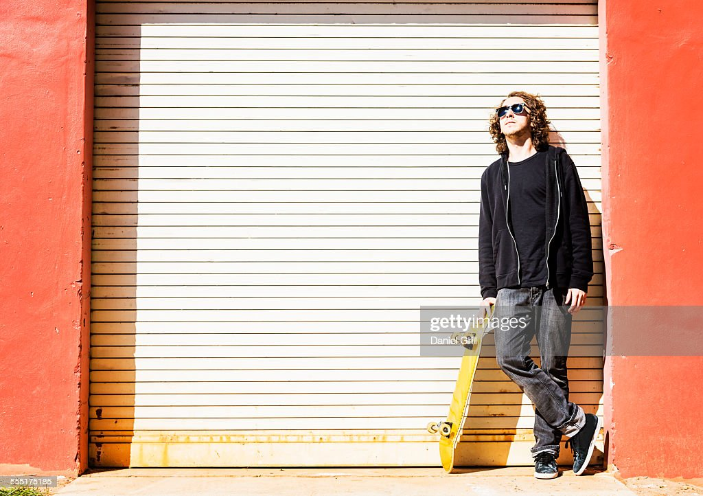 Usa Florida West Palm Beach Man With Skateboard Leaning On Garage