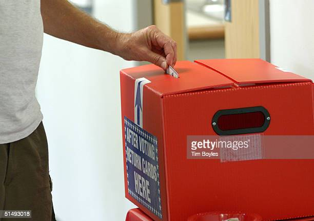 Floridian drops his ballot receipt into a box after using an electronic machine to vote on the first day of early voting in the presidential election...