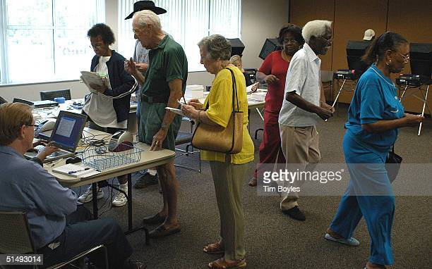 Floridians at left sign in before using electronic machines to cast their ballots on the first day of early voting in the presidential election at...