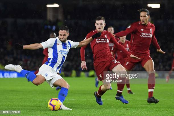 Florin Andone of Brighton Hove Albion crosses under pressure from Andrew Robertson and Virgil van Dijk of Liverpool during the Premier League match...