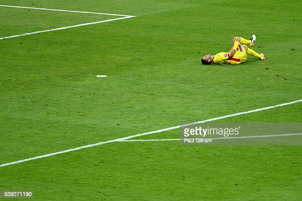 Florin Andone of Romania lies injured during the UEFA Euro 2016 Group A match between France and Romania at Stade de France on June 10 2016 in Paris...