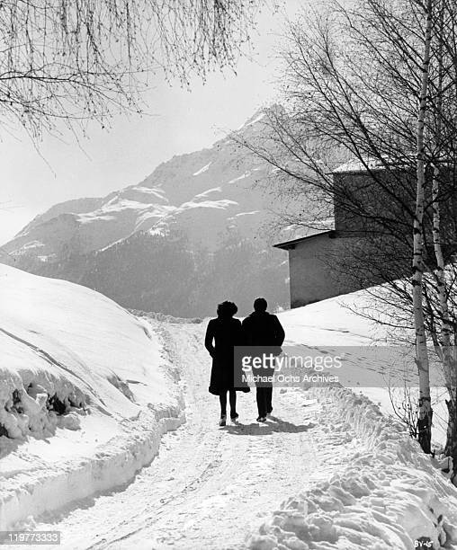 Florinda Bolkan walking with Daniel Quenaud on snow covered road in a scene from the film 'A Brief Vacation' 1973