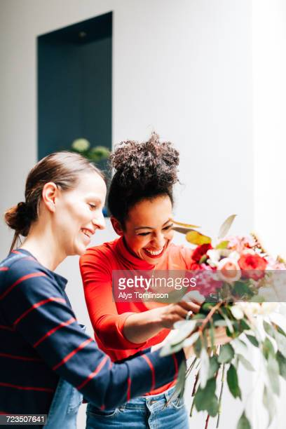 florist and student arranging bouquet at flower arranging workshop - arranging stock pictures, royalty-free photos & images