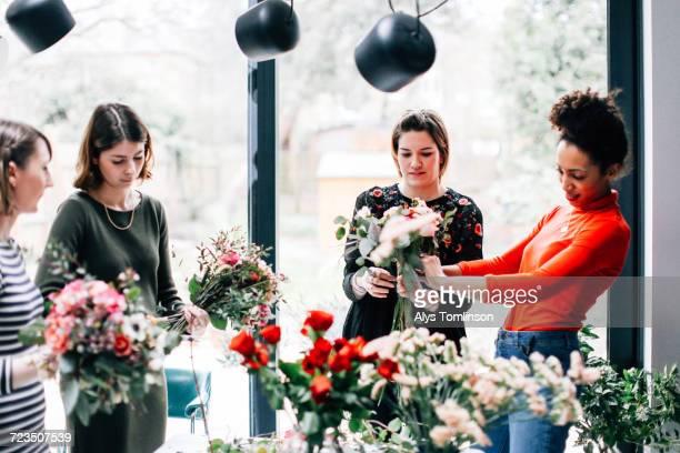 Florist and students arranging bouquets at flower arranging workshop