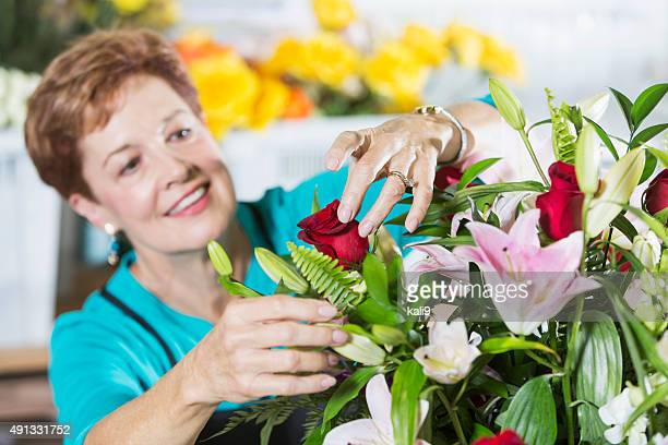 florist arranging bouquet of flowers in vase - kali rose stock pictures, royalty-free photos & images