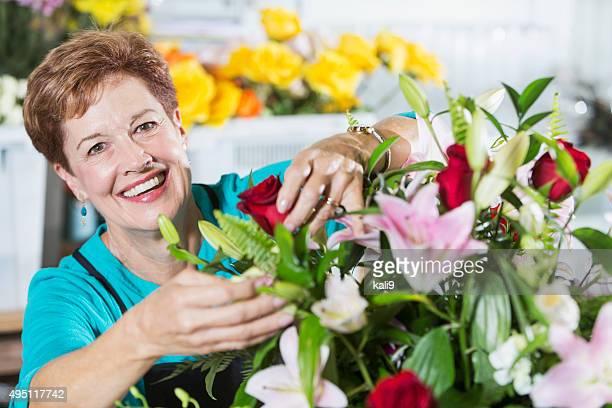 Florist arranging bouquet of flowers in vase