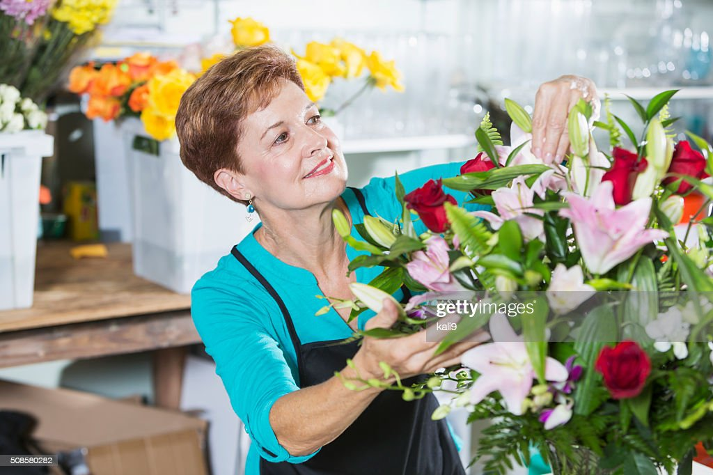 Florist arranging bouquet of flowers in vase : Stockfoto