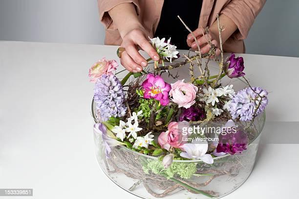 A florist arranging flowers in a glass bowel vase