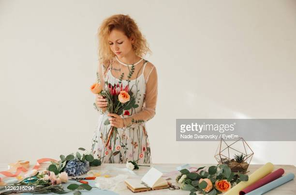 florist arranging flowers while standing at table against white background - arranging stock pictures, royalty-free photos & images