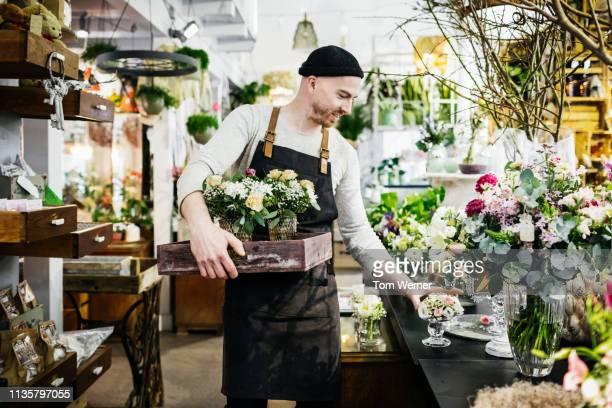 florist arranging his shop display - florist stock pictures, royalty-free photos & images
