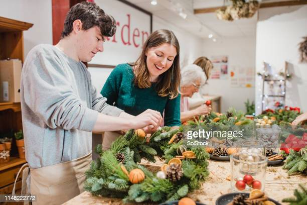 florist assisting a customer in a workshop - wreath stock pictures, royalty-free photos & images