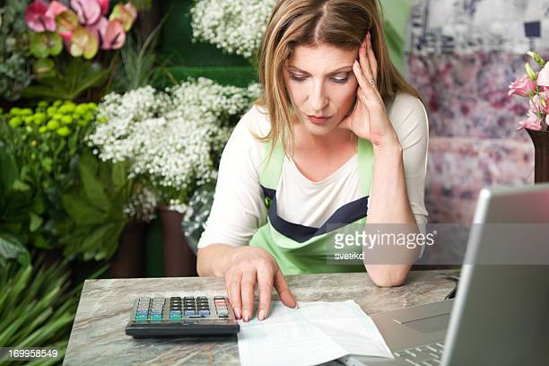 Florist at work paying bills.