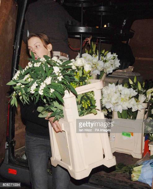 A florist carries flowers from a vehicle outside the Guildhall in Windsor Wednesday December 21 ahead of the civil partnership of Sir Elton John and...
