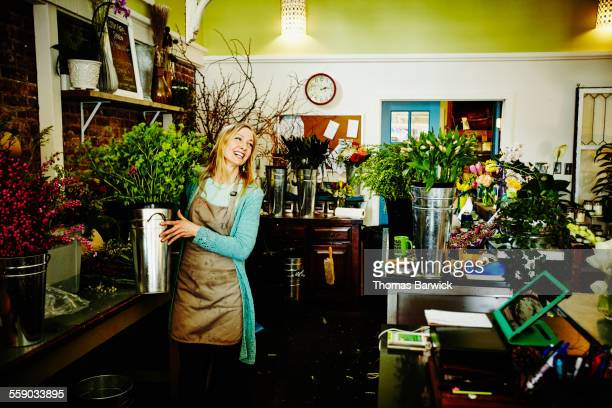 florist carrying bucket filled with flowers - happy merchant stock pictures, royalty-free photos & images