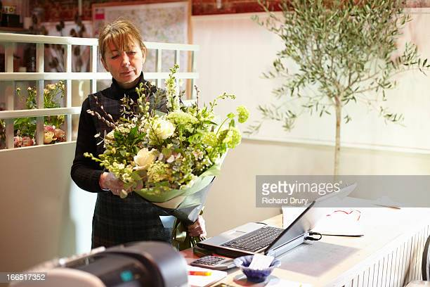 Florist checking bouquet of flowers