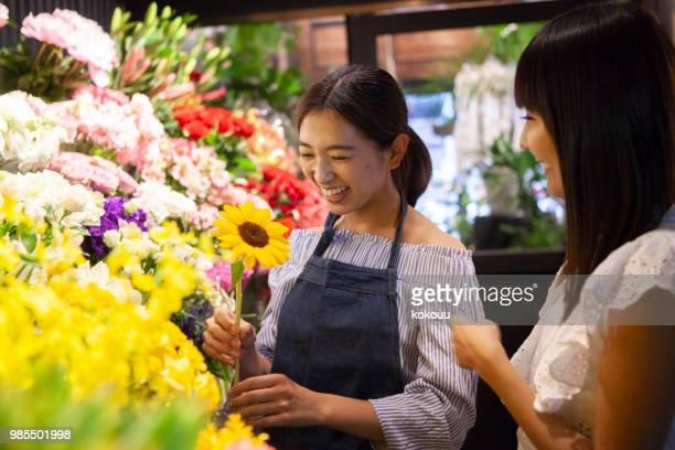 de klerk van een bloemist en een jonge gast. - klanten georiënteerd stockfoto's en -beelden