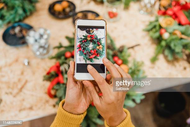 florist creating social media content - wreath stock pictures, royalty-free photos & images