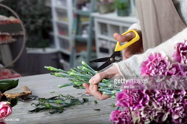 florist cutting flower with pruning shears