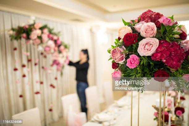 florist finishing their part of job for wedding in banquet hall - banquet hall stock pictures, royalty-free photos & images