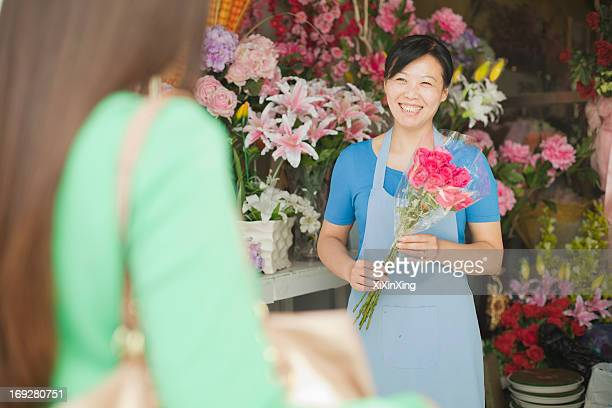 Florist Giving Bunch Of Flowers To Customer