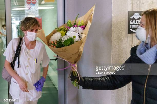 A florist hands a bouquet of flowers to a health worker outside the Burgos Hospital on March 21 in Burgos in northern Spain Spain reported a 32...