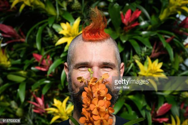 Florist Hank Roling poses with a Vanda orchid during a press preview of the Thai Orchid Festival at Kew Gardens on February 8 2018 in London England...