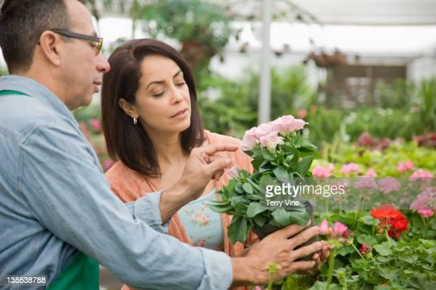 Florist helping customer in nursery