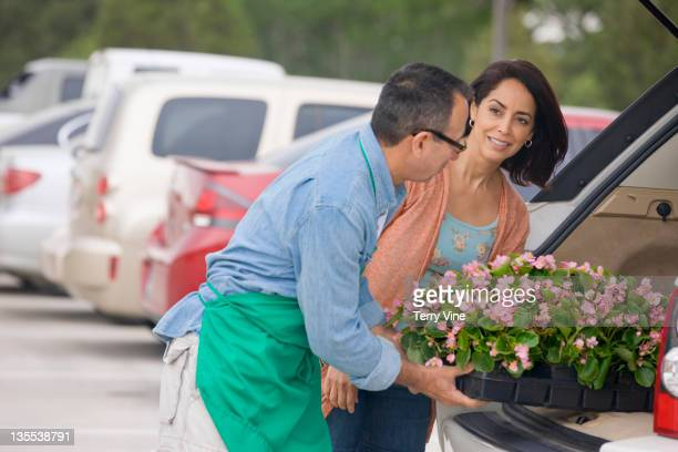 Florist helping customer load flowers into car