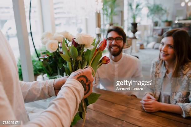 Florist in flower shop arranging bouquet for customers