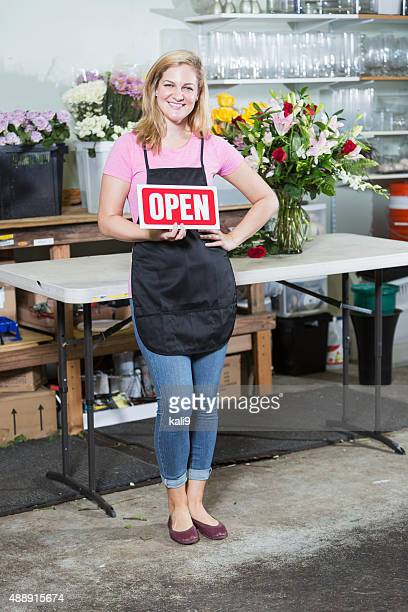 florist in flower shop holding open sign - kali rose stock pictures, royalty-free photos & images