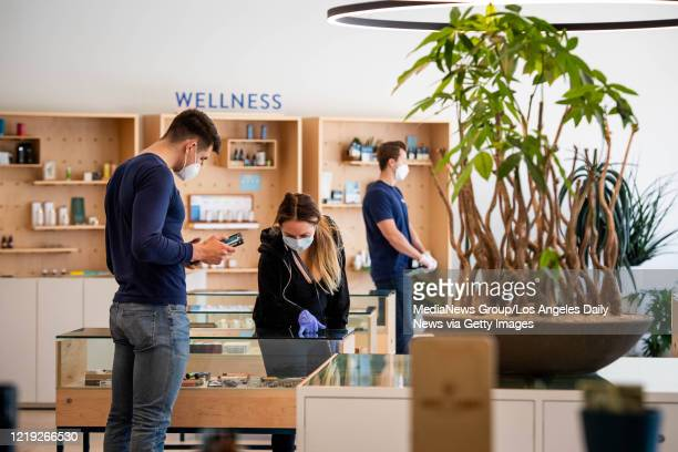 Florist Jared Keim assists Prisila at Sweet Flower, a licensed cannabis shop, in Studio City on Thursday, April 16, 2020 during the coronavirus...