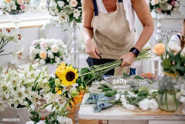 florist making floral arrangement - florist stock pictures, royalty-free photos & images