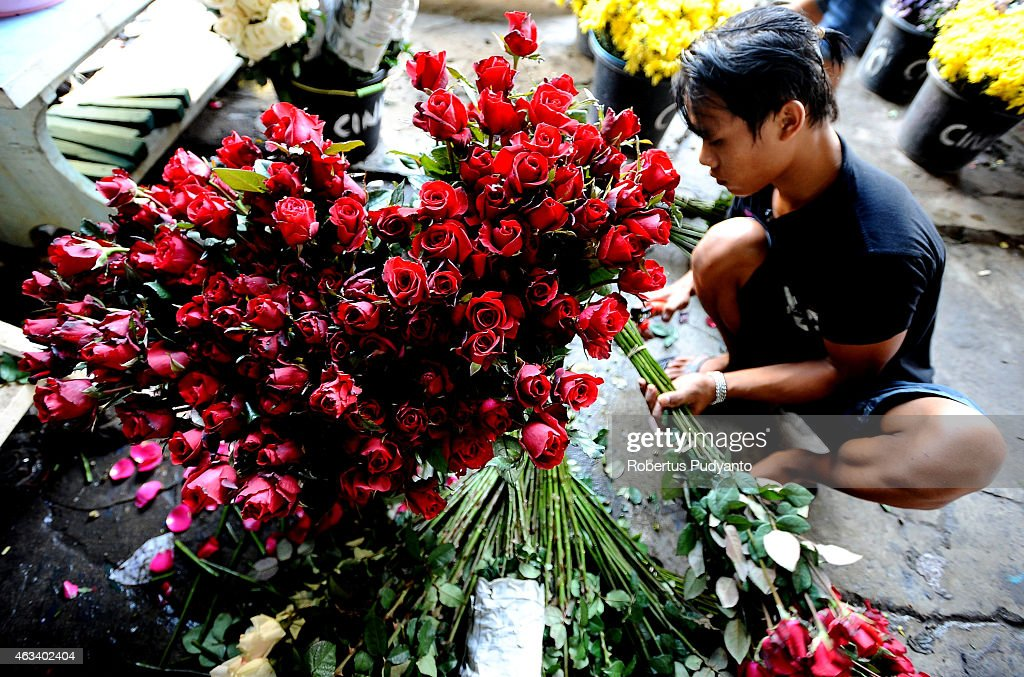A florist prepares roses at a traditional flower market during Valentines Day on February 14, 2015 in Surabaya, Indonesia. Roses, chocolates, teddy bears, toy hearts, candles, and cards are all part of the Valentines Day and orders increase significantly in the weeks leading up to the Valentines Day which celebrated on February 14th.