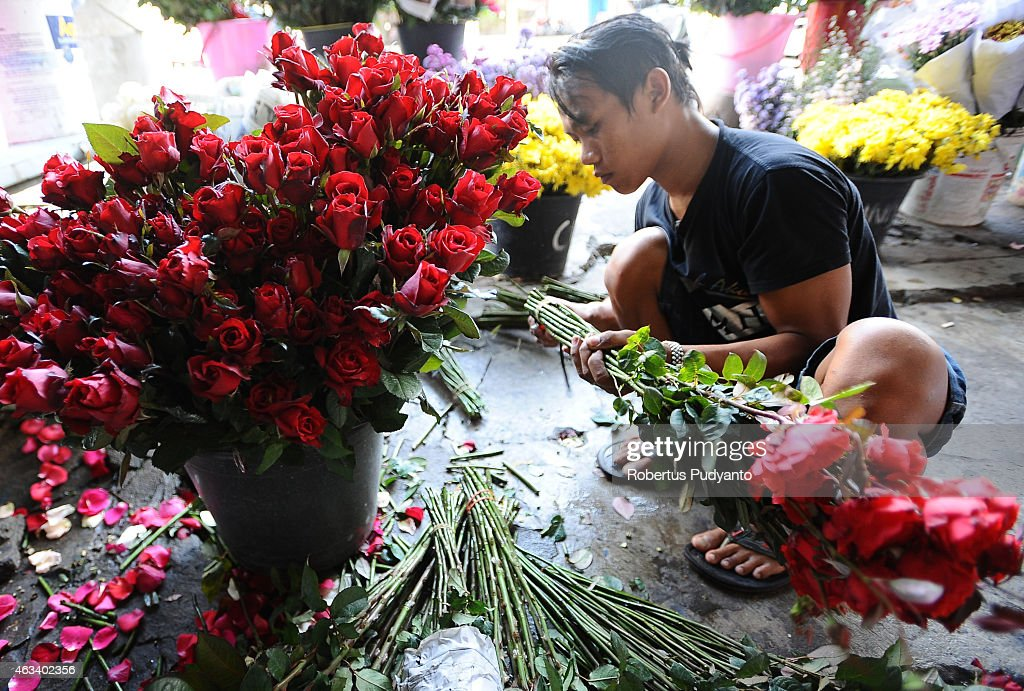 A florist prepares roses at a traditional flower market during the Valentines Day on February 14, 2015 in Surabaya, Indonesia. Roses, chocolates, teddy bears, toy hearts, candles, and cards are all part of the Valentines Day and orders increase significantly in the weeks leading up to the Valentines Day which celebrated on February 14th.